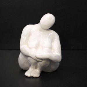 Escultura cerámica femenina sentada, acabado blanco