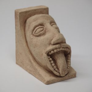 Sujetalibros basado en un canecillo románico con la figura de una cara grotesca