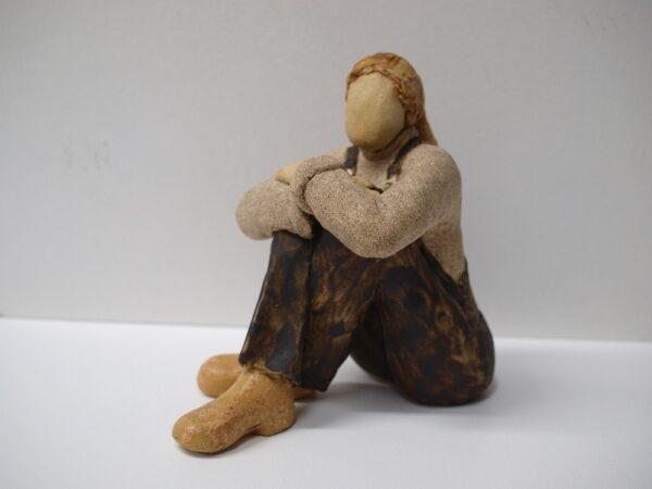 Escultura que representa un a chica sentada en el suelo
